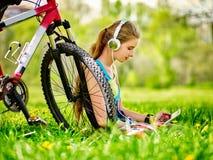 Bicis que completan un ciclo el reloj de las auriculares de la muchacha que lleva en tableta de la PC cerca de la bicicleta Foto de archivo