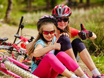 Bicis que completan un ciclo a la familia feliz que se sienta cerca de las bicicletas Fotografía de archivo