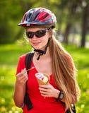 Bicis que completan un ciclo a muchachas con la mochila que completa un ciclo comiendo el cono de helado en parque del verano Imagen de archivo libre de regalías