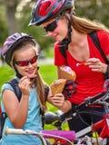 Bicis que completan un ciclo a muchachas con la mochila que completa un ciclo comiendo el cono de helado en parque del verano Fotos de archivo