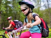 Bicis que completan un ciclo a muchachas con la mochila que completa un ciclo en parque del verano Foto de archivo libre de regalías