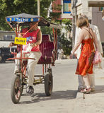 Bicitaxi in Havana. Three wheel taxi(bicitaxi) driver stops to pick up tourists on a street in havana,cuba Royalty Free Stock Photos