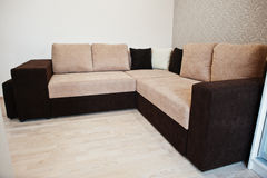 Bicolor cofee corner sofa bed at light room Royalty Free Stock Images