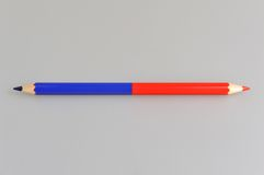 Bicoloured red and blue pencil on gray Stock Image