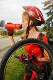 Bicycle автошина нагнетая велосипедом ремонта девушки велосипедиста ребенка на дороге Стоковые Изображения RF