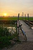 Bicycle на деревянной загородке моста на заходе солнца Стоковые Изображения RF