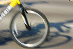 Bicycle. Panned motion of the front wheel of a bicycle with shadow of rider Stock Images
