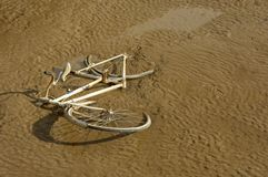 Bicycle. Old unwanted bicycle tipped in muddy riverbank Royalty Free Stock Image