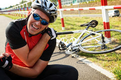 Bicycle accident. Biker holding his shoulder Royalty Free Stock Photo