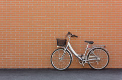 Bicycle against a Brick Wall. A city bike leaning against a red brick wall stock photography