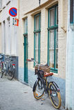 Bicycle against brick wall in Brugge Stock Images