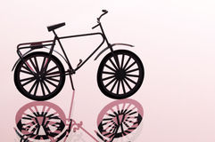 Bicycle against light red background Royalty Free Stock Photos