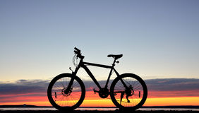 Bicycle against a sunset Stock Photos