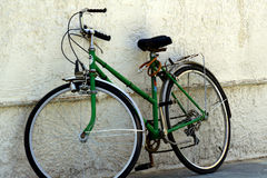 Bicycle against wall. An old bicycle in our front yard stock images