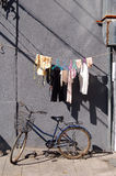 Bicycle airing clothes wall Royalty Free Stock Photography