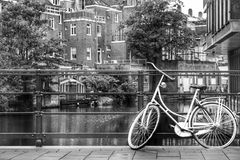 A bicycle and an amsterdam canal. A bicycle on the railings of a canal in amsterdam, the netherlands Royalty Free Stock Images