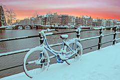 Bicycle in Amsterdam the Netherlands covered in snow. At sunset Stock Photos
