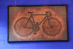 Bicycle Art Made of Pennies Against Blue Wall. A large picture of a bicycle made with pennies hanging against a blue cinder block wall royalty free stock images