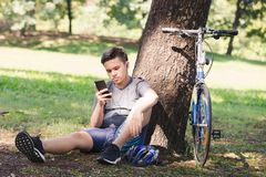 Bicycle. Asian young man bicycle standing by tree and listening to music with earphone Royalty Free Stock Photos