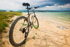 Bicycle on a bank of blue lake Royalty Free Stock Photography
