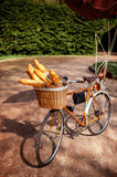 Bicycle with basket full of baguettes standing in the park Stock Photo