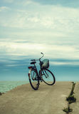 Bicycle at the beach on cloudy sky background. vintage retro sty Royalty Free Stock Image
