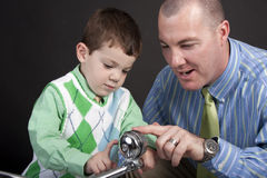 Bicycle bell. Father and young son looking at a bell on the handlebars of a tricycle Stock Images
