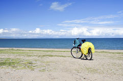 Bicycle by blue lake. A bicycle is standing by the blue lake under the blue sky with white clouds Stock Photos