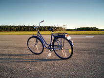 Bicycle. Blue bicycle standing at airbase runway during sunset with forest on background Stock Photography
