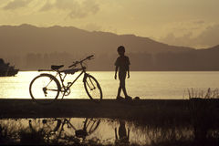 Bicycle Boy. Boy stands next to his  bicycle by the seashore Royalty Free Stock Image
