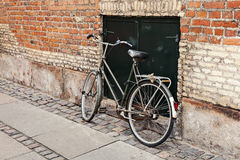 Bicycle by brick wall Stock Photo