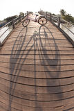 Bicycle on the bridge. Shadow of bicycle on the wooden bridge in the morning Royalty Free Stock Images