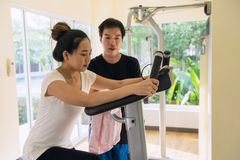 Bicycle cardio leg exercise with coach. Asian healthy girl exercise legs cardio training on bicycle in fitness gym with her boyfriend coach. Beautiful women work Stock Photos
