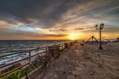 Bicycle and catapult in Alghero seafront at sunset Royalty Free Stock Photography
