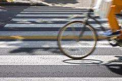 Bicycle cavaleiros no cruzamento pedestre no borrão de movimento Fotografia de Stock Royalty Free