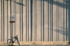 Bicycle chained to street sign. With textured vertical lines wall Stock Photo