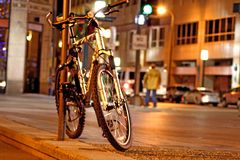 Bicycle in the city. Bicycle tied to a pole at night while traffic passes by Royalty Free Stock Photos