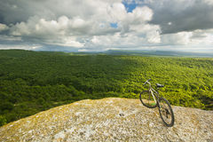 Bicycle on a cliff with covered by forest hills Royalty Free Stock Photo