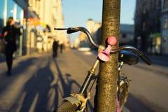 Bicycle com um sinal cor-de-rosa em uma árvore na rua Fotografia de Stock