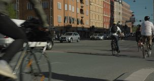 Bicycle commuters crossing an intersection in central Stockholm. Anonymous people shot in slow motion, 4K. stock video footage