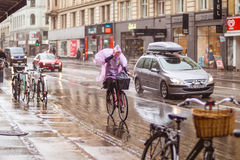 Bicycle in Copenhagen. Woman on bicycle on rainy day. Bicycle is common way of transportation in Denmark Royalty Free Stock Photography