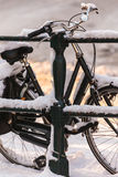 Bicycle covered with snow on a canal bridge Royalty Free Stock Images