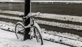 Bicycle covered with snow in a street royalty free stock image