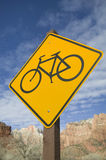 Bicycle Crossing Sign. Yellow bicycle crossing sign against blue sky and butte background Royalty Free Stock Photo