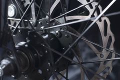 Bicycle disk brake installed in front wheel. Disk brake of the mountain bicycle on a black background a close up Stock Image