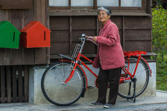 Bicycle and elderly woman Stock Photos