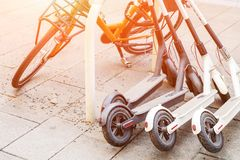 Bicycle and electric scooters parked on city street. Self-service street transport rental service. Rent urban vehicle with. Smartphone application. Zero royalty free stock photos