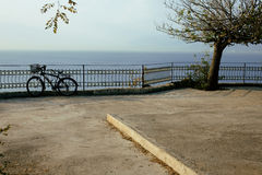 Bicycle on embankment at sea, garden with nobody Royalty Free Stock Photo