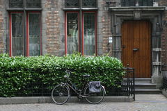 Bicycle in Europe. This is a picture of a bicycle resting on a fence in front of a house in Bruges, Belgium stock photo