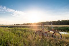 Bicycle in the field near the river. Stock Image
